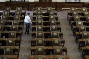 """Chris Currens, who works in the office of the sergeant-at-arms in the Texas House, walks through an empty chamber, Wednesday, Aug. 16, 2017, in Austin, Texas. The Texas Legislature had adjourned Tuesday and a Texas """"bathroom bill"""" targeting transgender people died again along with many of Republican Gov. Greg Abbott's summer demands. The Texas House will vote in January for its next speaker. (AP Photo/Eric Gay)"""