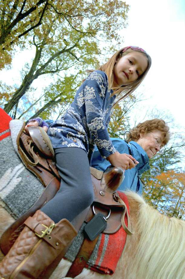 Above, Lindsley Swenson, 7, of Darien, takes a pony ride, assisted by Denise Fischer of Pied Piper Pony Rides of Patterson, N.Y., at The Mather Homestead's 2nd annual Homestead Harvest Fest, Saturday, Nov. 3, 2018, in Darien, Conn. Photo: Jarret Liotta / For Hearst Connecticut Media / Darien News Freelance