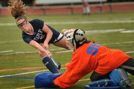 Staples' Kyle Kirby scores a goal with a shot past the shoulder of diving Fairfield Ludlowe goalie Grace Ghee on Sept. 24.