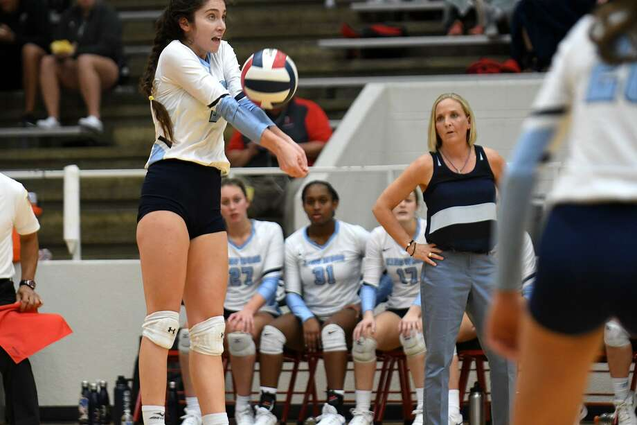 Kingwood senior outside hitter Peyton Shamp, center, makes a play in front of Mustangs head coach Christie Mewis during the first set of their UIL Region III Class 6A Area Volleyball Playoff versus Pearland Dawson at Phillips Fieldhouse in Pasadena on Nov. 1, 2018. Photo: Jerry Baker, Houston Chronicle / Contributor / Houston Chronicle
