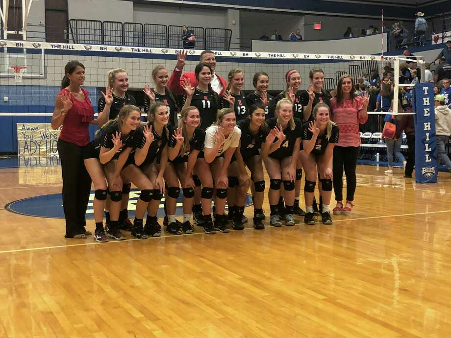 The Hargrave volleyball team poses after beating Hamshire-Fannett in the Regional Quarterfinals. They hold up four fingers for advancing to the fourth round of the playoffs. Photo: Elliott Lapin / Staff Photo