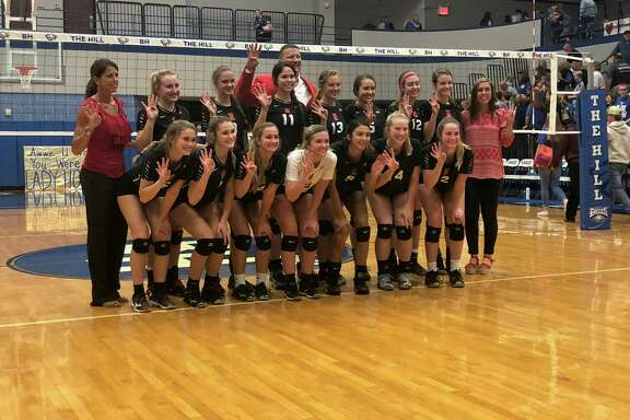 The Hargrave volleyball team poses after beating Hamshire-Fannett in the Regional Quarterfinals. They hold up four fingers for advancing to the fourth round of the playoffs.