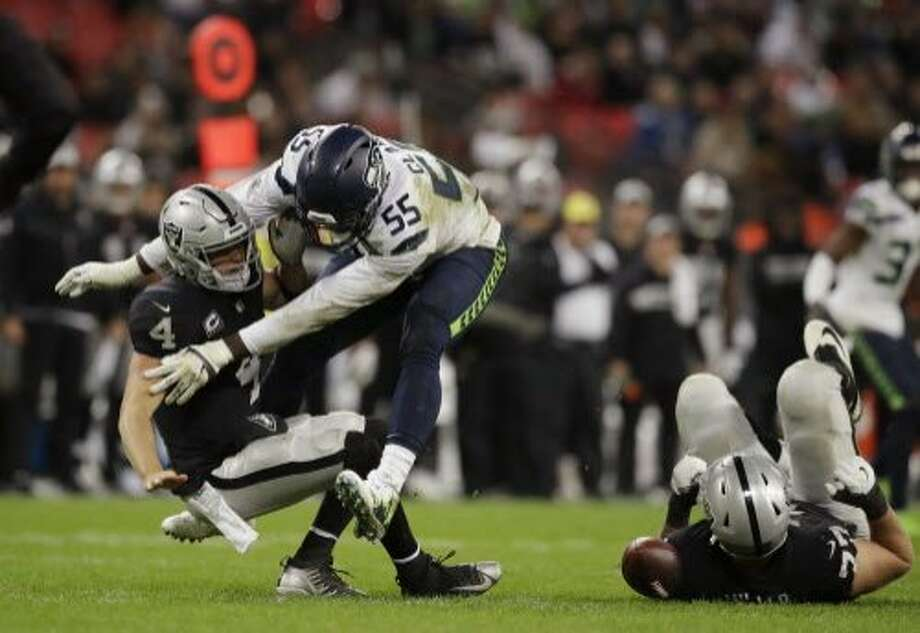 FILE - In this Oct. 14, 2018, file photo, Oakland Raiders quarterback Derek Carr (4) is sacked by Seattle Seahawks defensive end Frank Clark (55) during the second half of an NFL football game at Wembley stadium in London. After being well protected his first four seasons, Carr has been under heavy pressure the past few weeks and the results have not been good. (AP Photo/Matt Dunham, File) Photo: Matt Dunham / Associated Press