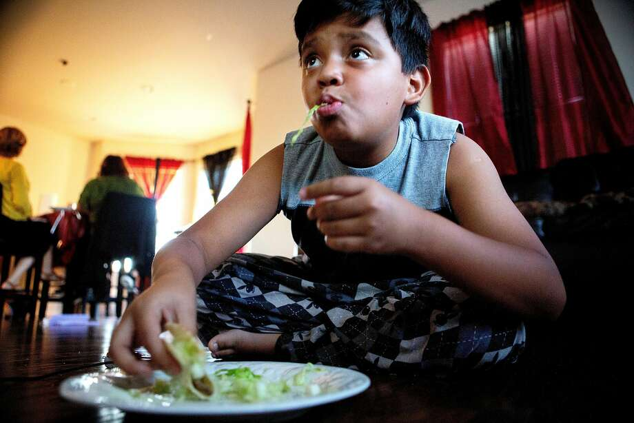Oscar Bernal, 10, watches a video game while eating a taco. Photo: Santiago Mejia / The Chronicle