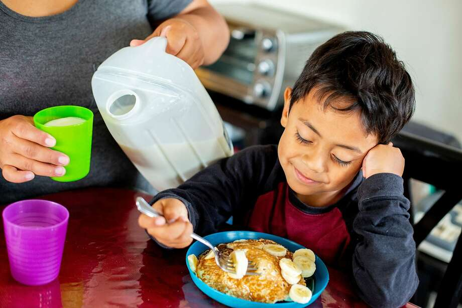Karla Yamileth Bernal Flores pours a cup of milk for her 10-year-old son, Oscar. Photo: Santiago Mejia / The Chronicle