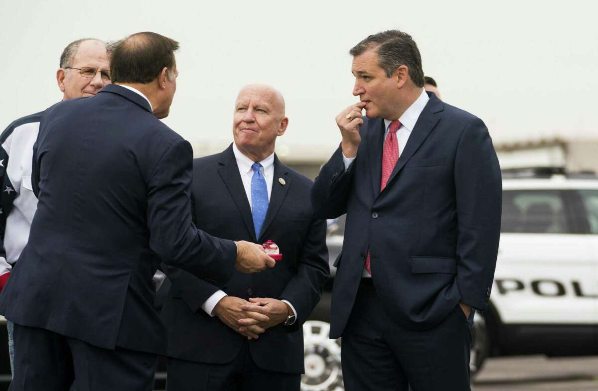 Sen. Ted Cruz (R-Texas) takes a mint, with Rep. Kevin Brady (R-Texas), center, before greeting President Donald Trump as he arrives at Ellington Field Joint Reserve Base in Houston, Oct. 22, 2018. Trump will be joining Cruz for a campaign rally. (Doug Mills/The New York Times)
