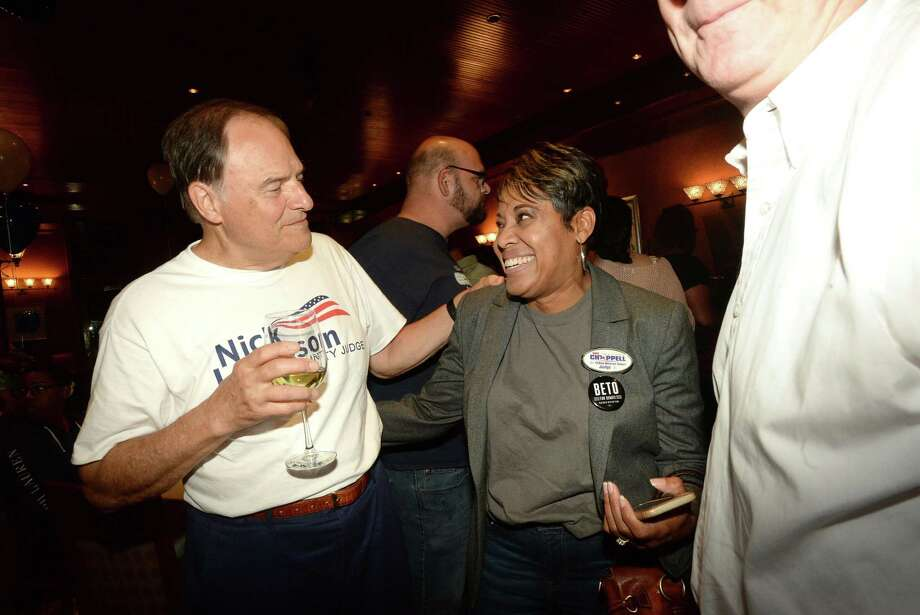 Jefferson County Judge Democratic candidate Nick Lampson jokes with Jackie Simien during a Democratic watch party at Suga's.