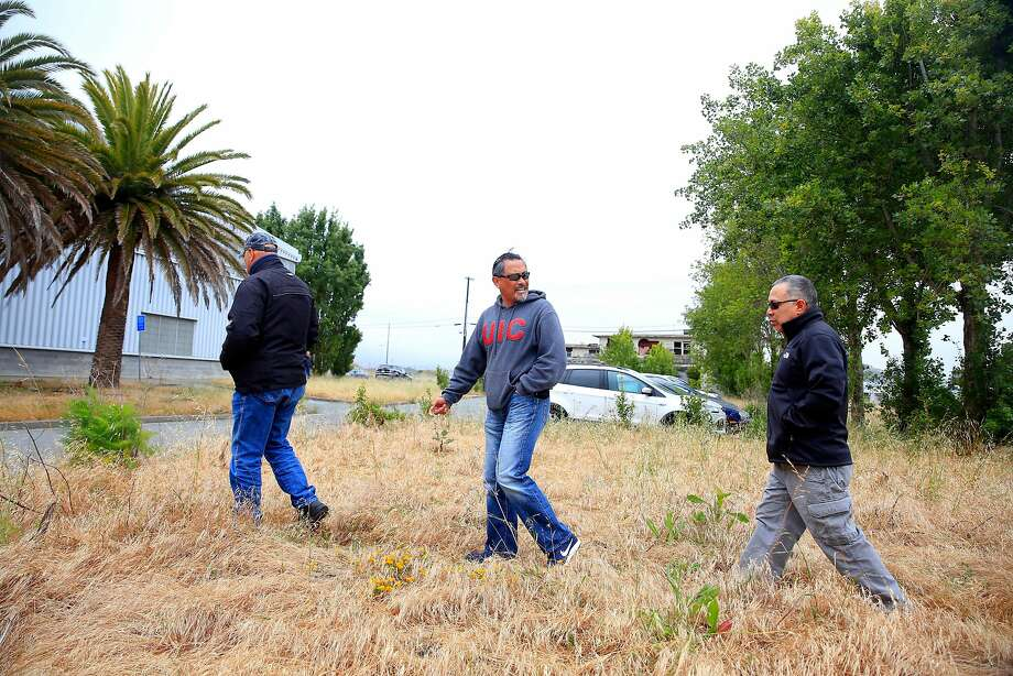 Paul Swiatko (left), Mel Bautista and Richard Tong, who were part of the San Francisco Police Department's tactical division, walk toward Building 606, where they used to work and train. Photo: Lea Suzuki / The Chronicle