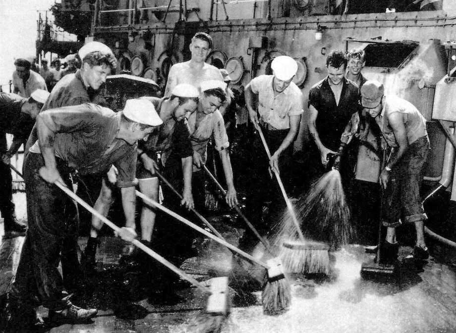 "Navy crews swab the deck of the Prinz Eugen in an attempt to reduce radiation levels after ""Shot Baker,"" the July 25, 1946 underwater detonation of a plutonium bomb at Bikini Atoll in the Marshall Islands. Dozens of vessels were hopelessly contaminated by gigantic radioactive waves and a curtain of poisoned mist. Photo: U.S. Naval Institute 1946"