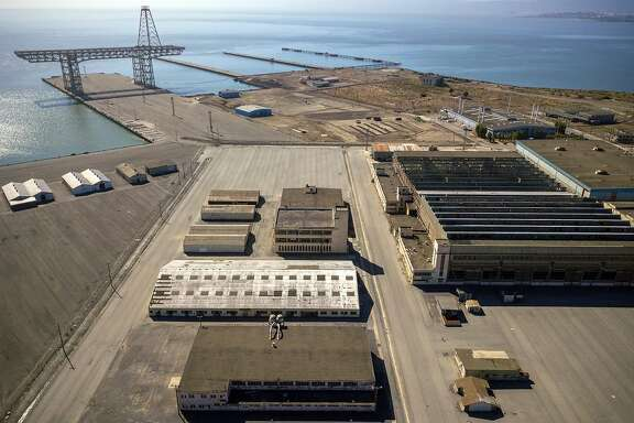 """Aerial photos of Hunters Point Naval Shipyard showing Buildings 366 (white on left, middle) 351, above that on the right, and 411 (middle on the right) in Parcel G in San Francisco, Calif., on Tuesday, September 11, 2018. The Navy's retesting plan for Parcel G is being brought into question. When the U.S. Navy pledged to perform new soil tests at its Superfund waste site in San Francisco, the priority was """"to protect the human health and the environment."""" But the Navy's re-testing plan is largely based on a cost-cutting report it paid a defense contractor to put together more than six years ago. What's more, the old report relies on data collected by Tetra Tech, the cleanup firm that submitted fake measurements and got caught. It essentially advocates for lowering cleanup standards and leaving more radioactivity in the ground.  Multiple government agencies have now come out against the Navy?s plan to re-test Parcel G, saying that it could put public health at risk if it is not changed. Environmental experts agree and say even if the Navy listens to those agencies the plan is flawed and falls far short of what was promised in the wake of the Tetra Tech fraud revelations."""