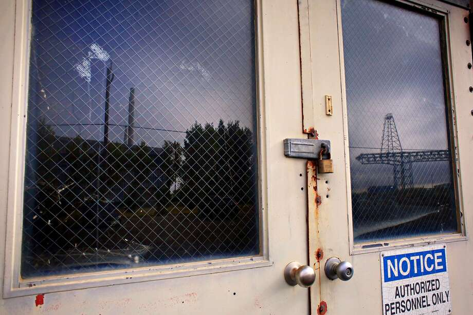 Building 606 is reflected in the window of another shipyard building. Photo: Lea Suzuki / The Chronicle