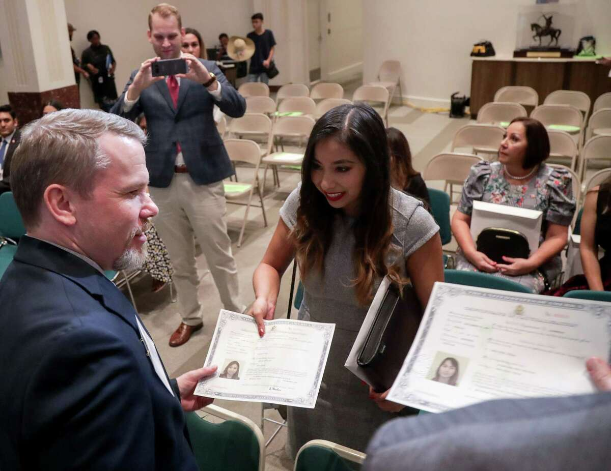 Miriam Arellano smiles as she gets her citizen documents after a naturalization ceremony at Houston City Hall, Wednesday, Nov. 7, 2018, in Houston. Arellano was brought from Mexico as an undocumented immigrant when she was less than two years old.