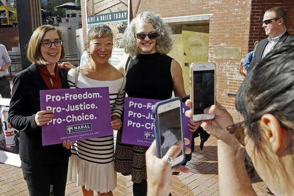 FILE - In Oct. 17, 2018 file photo, Oregon Gov. Kate Brown, left, poses for photos with supporters after a rally in Portland, Ore. Even in deep-red states, voters embraced an array of liberal-backed ballot measures in Tuesday's election. In Oregon, voters soundly rejected a measure that would have banned the use of public money to pay for abortion coverage. The measure would have left low-income women on the state's Medicaid plan to pay out-of-pocket for abortions and would have eliminated abortion coverage for public employees such as teachers and firefighters who receive health coverage under a state plan. (AP Photo/Don Ryan, File)