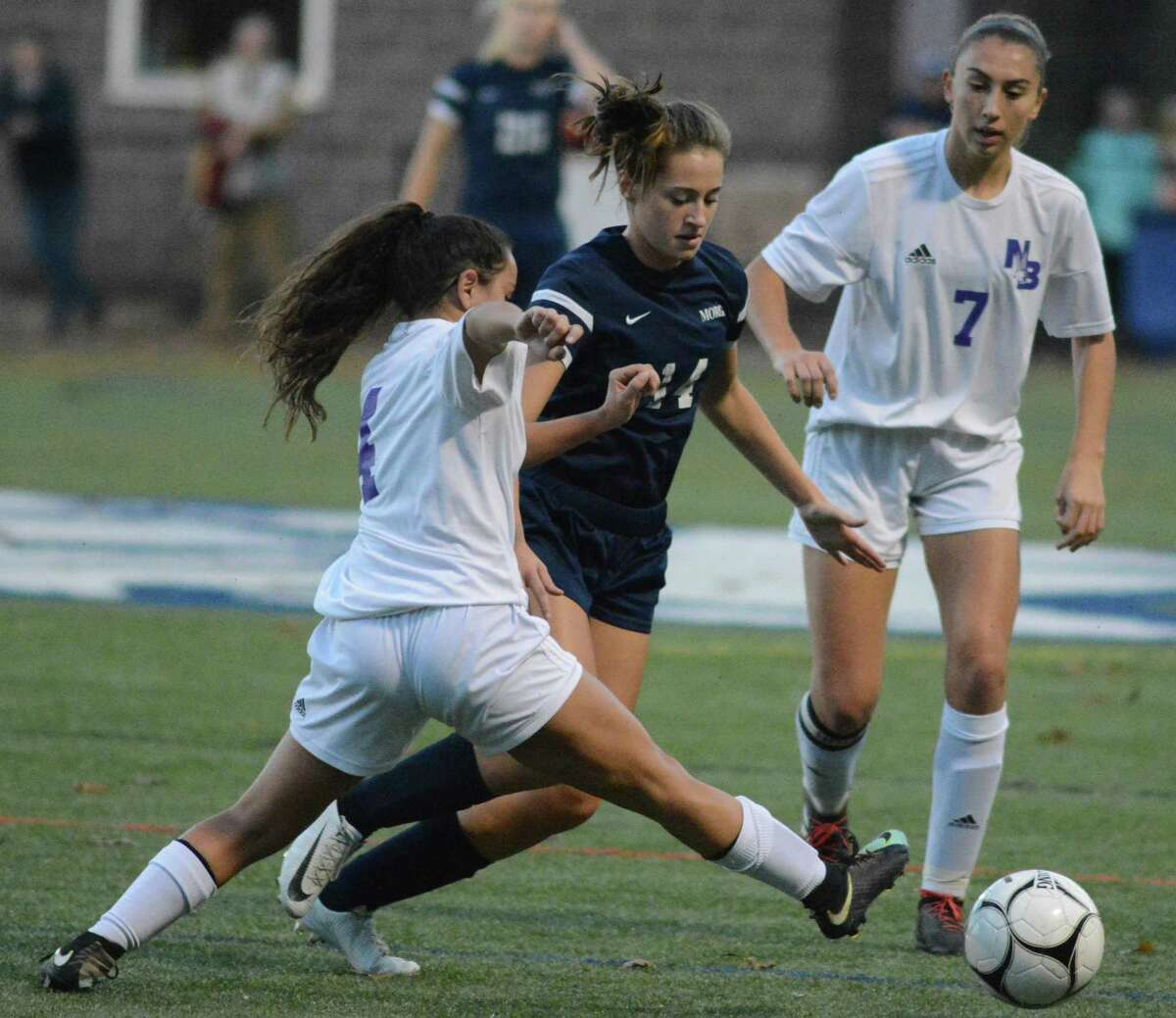 Morgan's Kylee Clifton (14) is defended by North Branford's Gabbie Sarmento (4) and Ana Pavic (7) during a Class M girls soccer playoff game on Wednesday, Nov. 7, 2018 in Clinton, Conn. Morgan won 2-1.