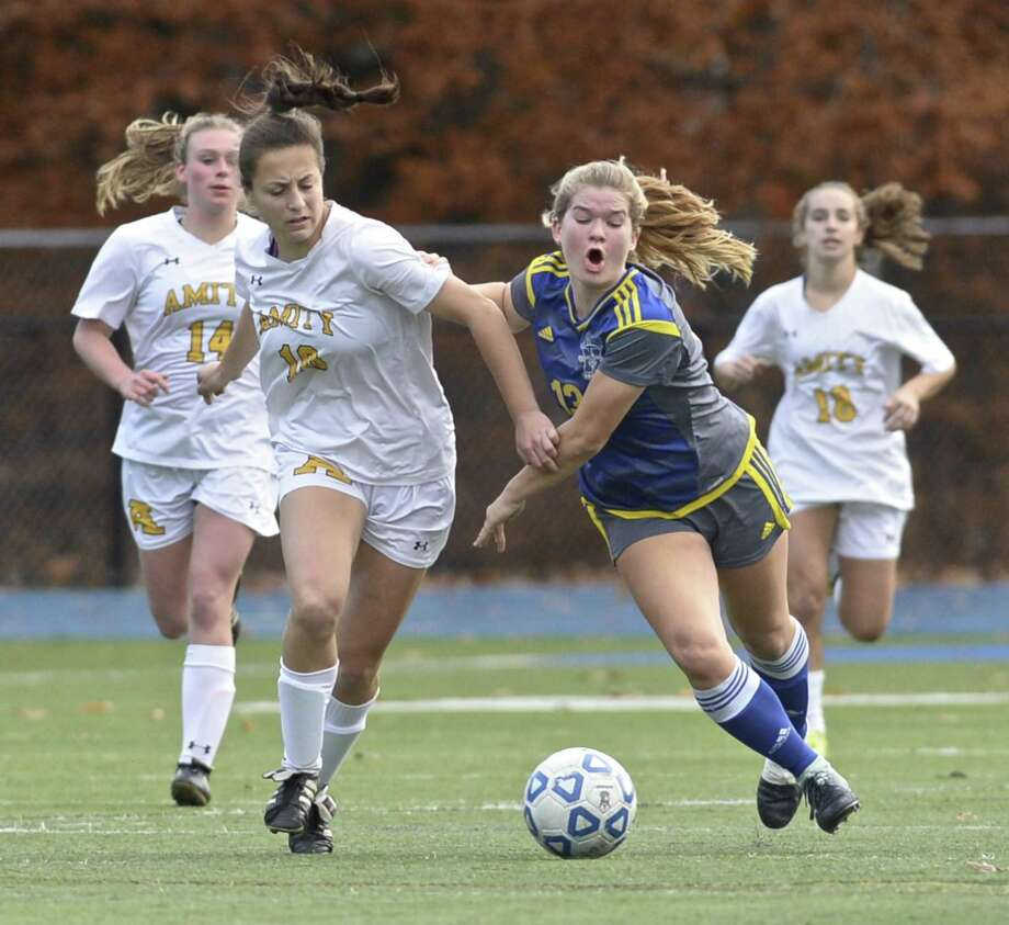 Amity's Laurella Marin (10) and Newtown's Emma Curtis (13) wrestle for the ball in the girls LL soccer game between Amity and Newtown high schools, Wednesday, November 7, 2018, at Newtown High School, Newtown, Conn. Newtown defeated Amity 1-0. Amity's Cailey Esposito (14) and Nicole Grosso (18) follow the play. Photo: H John Voorhees III / Hearst Connecticut Media / The News-Times