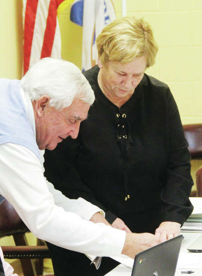 New Godfrey Village Board Member Ben Allen signs some paperwork for Village Clerk Pam Whisler after he was sworn in Wednesday. Allen, a local attorney and business owner, replaces the late Eldon Twirp Williams, who was murdered Oct. 16 in Alton.