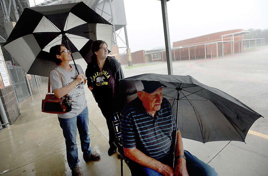 Torrie Teague shields herself and daughter Desireigh from a blowing rain as they, Jerry Neeb and other first-in-line fans huddle beneath the overhang at the ticket booth at Port Neches-Groves' stadium, braving the elements for their Mid-County Madness game tickets Wednesday. Photo taken Wednesday, November 7, 2018 Kim Brent/The Enterprise Photo: Kim Brent/The Enterprise