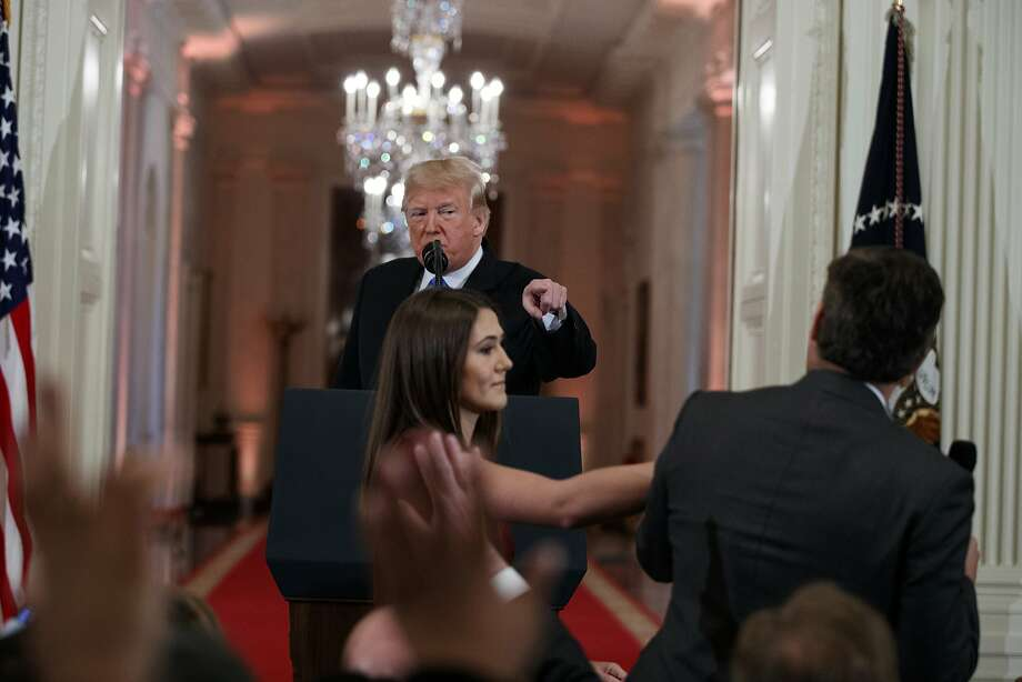 President Donald Trump watches as a White House aide reaches to take away a microphone from CNN journalist Jim Acosta during a news conference in the East Room of the White House, Wednesday, Nov. 7, 2018, in Washington. (AP Photo/Evan Vucci) Photo: Evan Vucci, Associated Press
