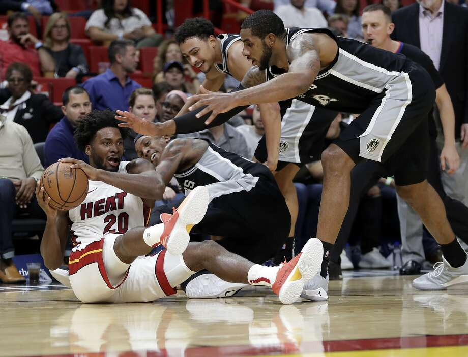 Miami Heat forward Justise Winslow (20) grabs a loose ball over San Antonio Spurs forward Dante Cunningham, left, guard Bryn Forbes, and forward LaMarcus Aldridge, right, during the second half of an NBA basketball game, Wednesday, Nov. 7, 2018, in Miami. The Heat won 95-88. (AP Photo/Lynne Sladky) Photo: Lynne Sladky, Associated Press