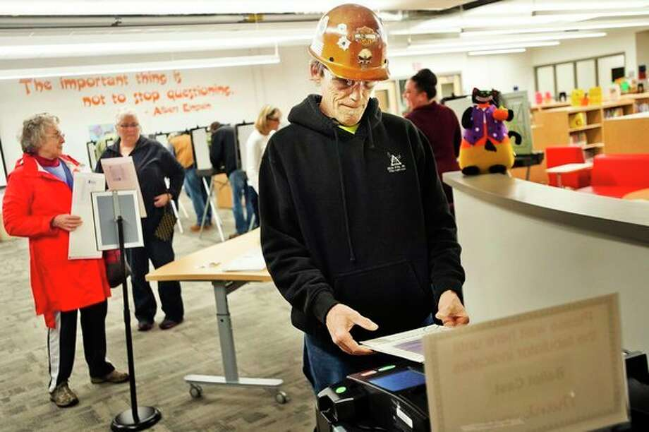 Midland resident Al Hubert enters his ballot into a tabulation machine while voting in the midterm elections on Tuesday, Nov. 6, 2018 at Central Park Elementary in Midland. (Katy Kildee/kkildee@mdn.net)
