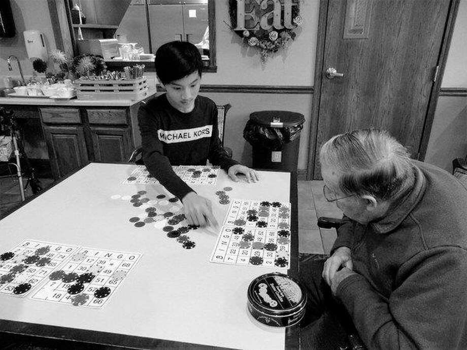 Jefferson CyDog team member Grant Wang helps a resident review his bingo board. (Photo provided)