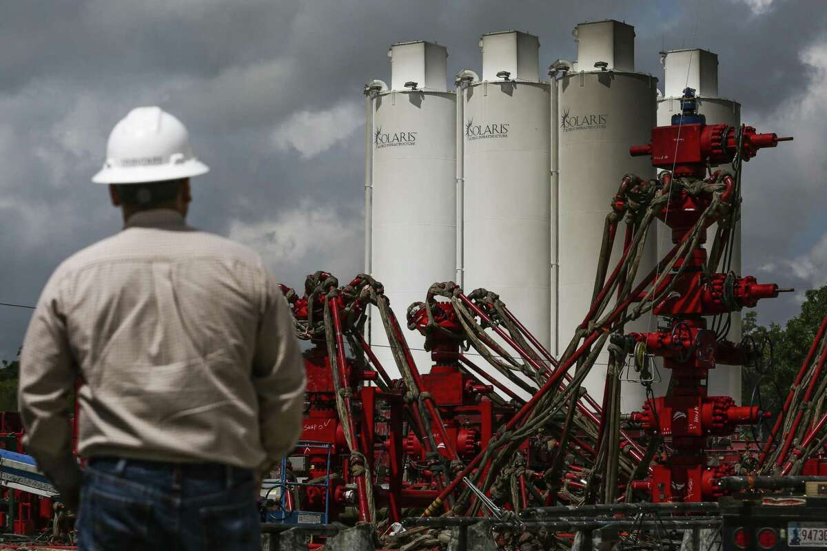 A WildHorse Resource Development employee overlooks fracking operations outside Caldwell. Wildhorse, of Houston, was recently acquired by Chespaeake Energy of Oklahoma City, one of several recent deals in the oil patch.