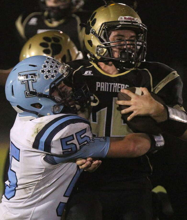 Triopia's Ben Stanberry holds onto a Camp Point Central running back during a game earlier this season. Photo: Dennis Mathes | Journal-Courier