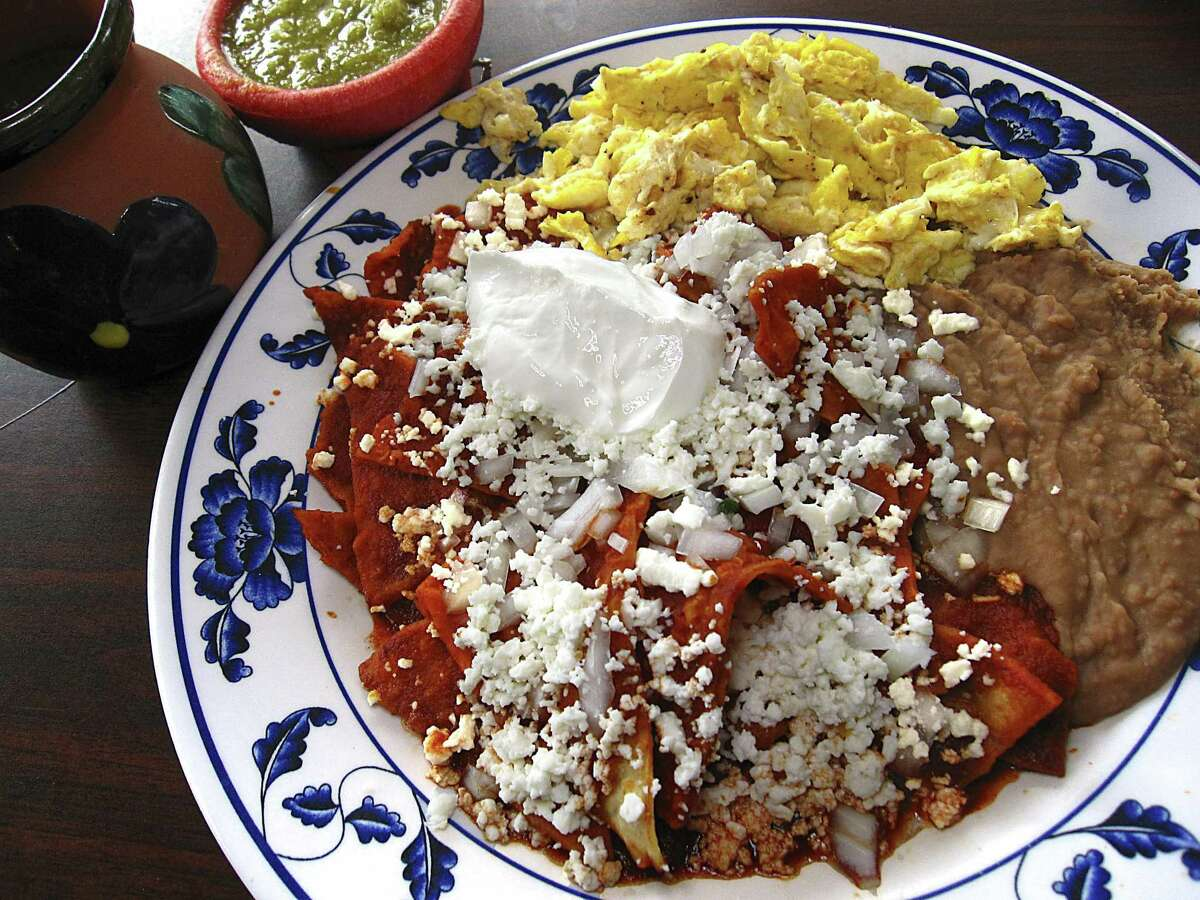 Mama Chuy's chilaquiles with chips, chile sauce, panela cheese and sour cream with sides of scrambled eggs, refried beans and a cup of the cinnamon-sugar coffee called cafe de olla from Las Sabrosas de Guanajuato.