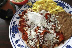 Mama Chuy's chilaquiles with chips, chile sauce, panela cheese and sour cream with sides of scrambled eggs, refried beans and a cup of the cinnamon-sugar coffee called café de olla from Las Sabrosas de Guanajuato.