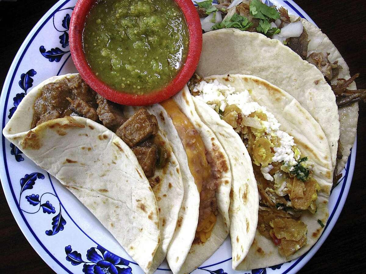 A plate of tacos - carne guisada, bean and cheese, migas with pico de gallo and carnitas with cilantro and onions - all on handmade tortillas, from Las Sabrosas de Guanajuato.