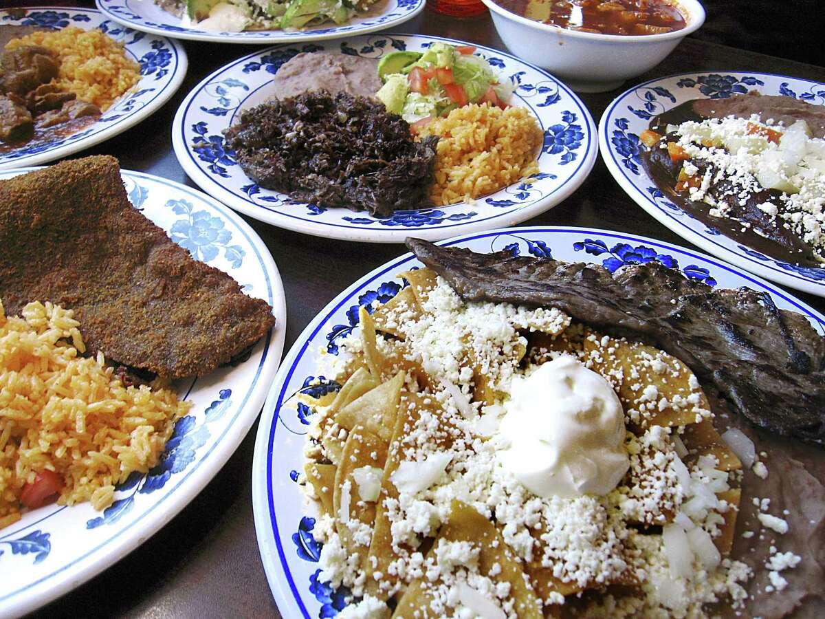 Dishes from Las Sabrosas de Guanajuato include, clockwise from foreground: Guanajuato-style chilaquiles with carne asada, beef milanesa, costillas de puerco, a Tony Taco Sabroso with beef fajitas, menudo, enmoladas with chicken in dark mole sauce and barbacoa.