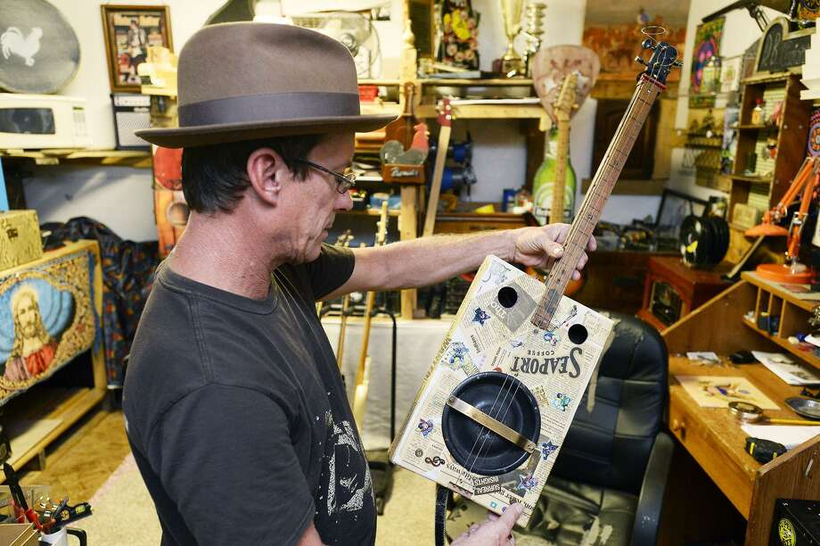 Donnie Badgett shows one of his cigar box guitars. Badgett builds instruments out of items her finds on the side of the road and junk sales. 