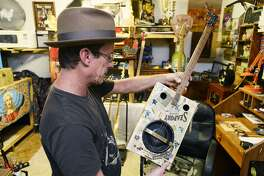 Donnie Badgett shows one of his cigar box guitars. Badgett builds instruments out of items her finds on the side of the road and junk sales. Photo taken Thursday 9/13/18 Ryan Pelham/The Enterprise