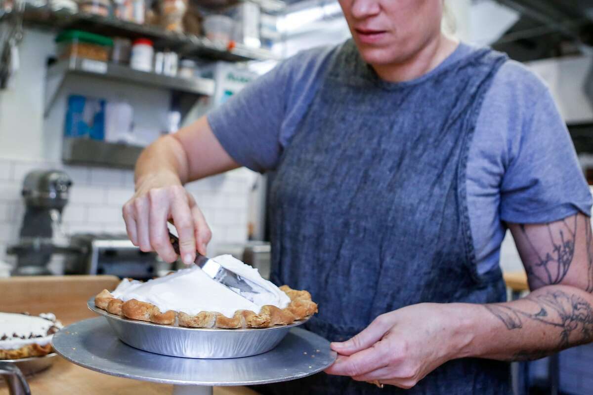 Black Jet Baking Co. owner Gillian Shaw adds whipped cream on top of a finished banana cream pies on Wednesday, November 7, 2018 in San Francisco, Calif.