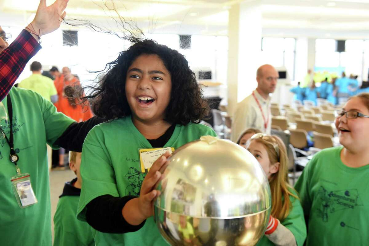 Gabrielle Casillas Valverde from from Lincoln Elementary in Scotia Glenville has a hair-raising moment when she is charged with static electricity during the annual Science Day at GE Global Research on Thursday, Nov. 8, 2018, in Niskayuna N.Y. General Electric scientists and engineers entertained local school children with science lessons and experiments. This the 29th year GE has held the event. (Will Waldron/Times Union)