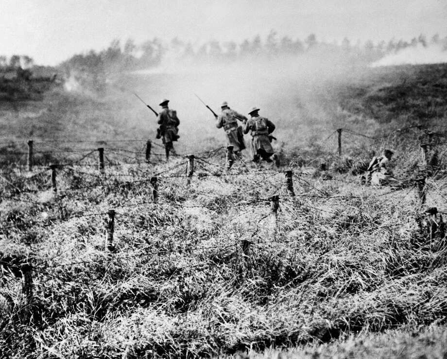 NINETY THREE OF ONE HUNDRED PHOTOS WORLD WAR ONE CENTENARY TIMELINE In this Sept. 13, 1918 file photo, U.S. troops of the 107th Regiment Infantry, 27th Division, advance on a path through a barbed wire entanglement near Beauqueanes, Somme, France during World War One. (AP Photo/U.S. Army Signal Corps, File) Photo: Associated Press / AP1918