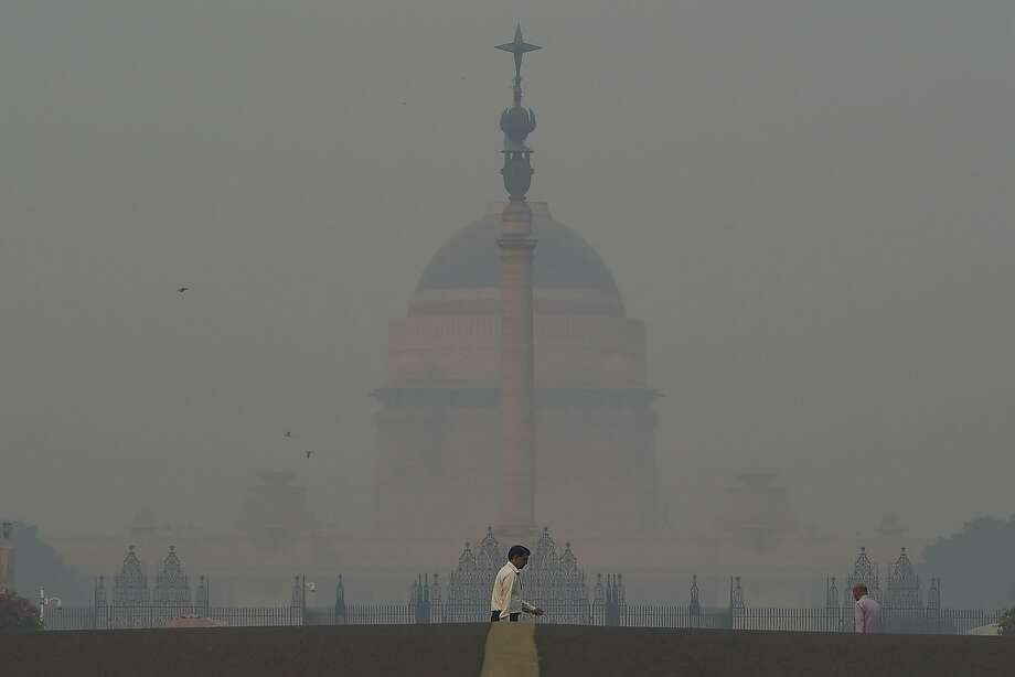 A pedestrian crosses a road amid heavy smog in New Delhi after a night of free-for-all fireworks. Photo: Money Sharma / AFP / Getty Images