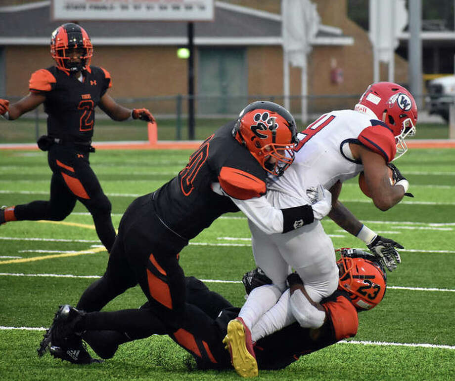 Edwardsville's Dionte Rodgers, bottom, and Adam Foster team up to tackle a West Aurora ball carrier in the first half of second-round action. Photo: Matt Kamp/Intelligencer