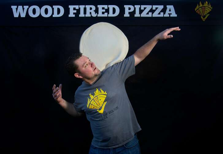 Justin Wadstein of Sleight of Hand Pizza shows off his pizza-tossing skills while selling pies at the Felton Farmers Market on Tuesday, 10/30, 2018 in Felton, California. Wadstein has won a dozen Las Vegas pizza-tossing world championships and is something of a local celeb.