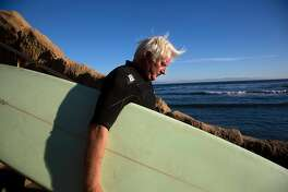 "Legendary surfer Richard ""Frosty"" Hesson heads out to catch some waves at Pleasure Point on Monday, 10/29, 2018 in Santa Cruz, California. Hesson was depicted by Gerard Butler in the film Chasing Mavericks."