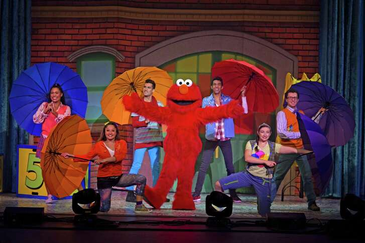"""Elmo, center in red, and his friends play on a rainy day in a scene from """"Sesame Street Live!"""""""