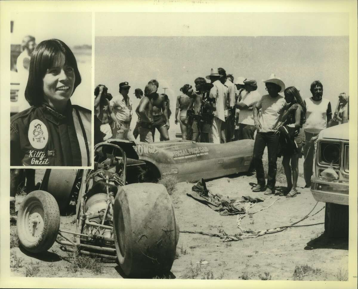 """Famed Hollywood stunt woman Kitty O'Neil, inset, is shaken but still smiling despite her narrow escape from a spectacular and totally unplanned wrecking of the race car, pictured here, in which she shattered land speed records during the filming of her record run for NBC-TV's two hour thrill packed """"Big Event"""" special """"Super Stunt 2"""" to be telecast."""