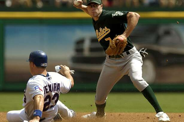 Oakland Athletics shortstop Bobby Crosby, right, tries to throw out Texas Rangers' David Dellucci at first base after getting the force out on Texas' Mark Teixeira at second during the third inning, Thursday, Sept. 23, 2004, in Arlington, Texas. Dellucci was safe at first. (AP Photo/Tony Gutierrez)