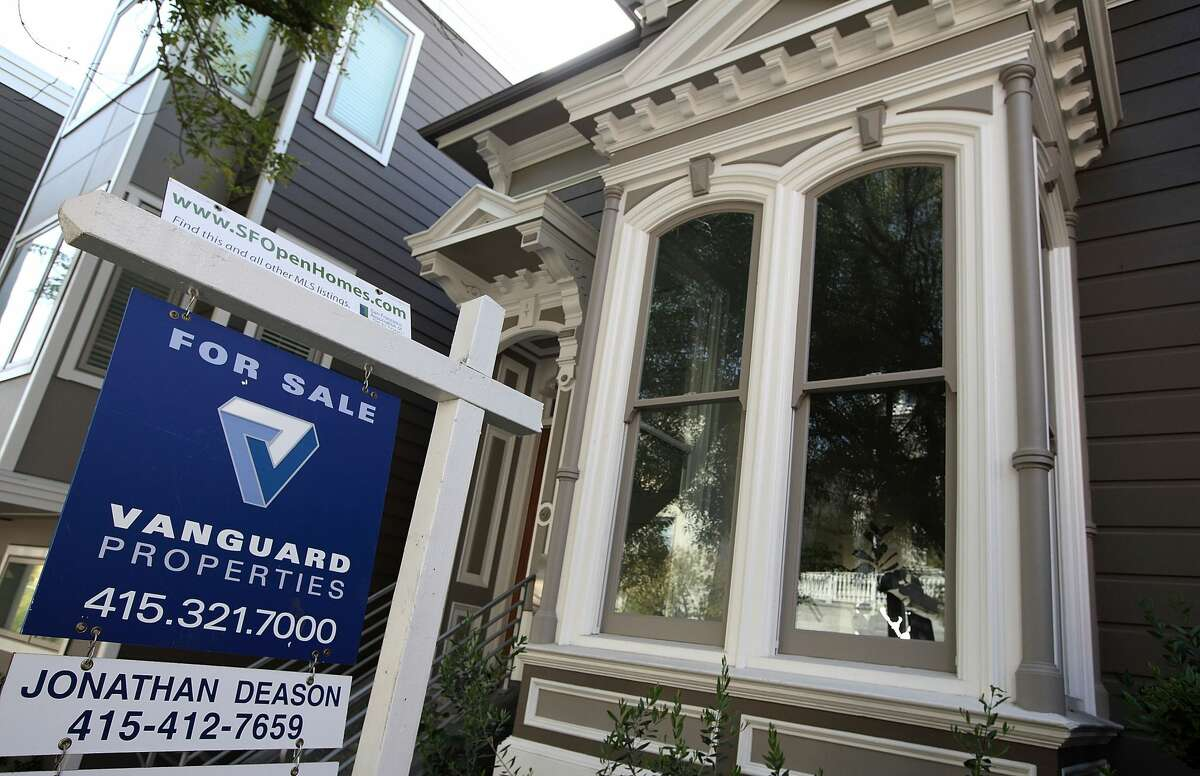 FILE: A sign is posted in front of a home that is for sale in San Francisco, California.