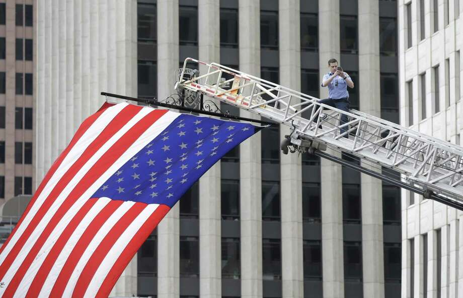 A Houston firefighter stands on an aerial ladder as a large flag is positioned over the start line during the Veterans Day Celebration and 9/11 Heroes Run at City Hall Saturday, Nov. 11, 2017, in Houston. The Houston 9/11 Heroes Run was postponed due to Hurricane Harvey. ( Melissa Phillip / Houston Chronicle ) Photo: Melissa Phillip, Houston Chronicle / Houston Chronicle / © 2017 Houston Chronicle