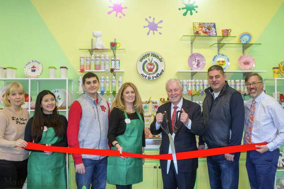 From left, Alina Dancho, Janice Eng, Matthew Ionescu, owner Alla Ionescu, First Selectman Mike Tetreau, owner Bob Ionescu, and Fairfield Community and Economic Development Director Mark Barnhart celebrate the opening of Happy Hands Art & Pottery on Oct. 26 in Fairfield. Photo: Contributed Photo