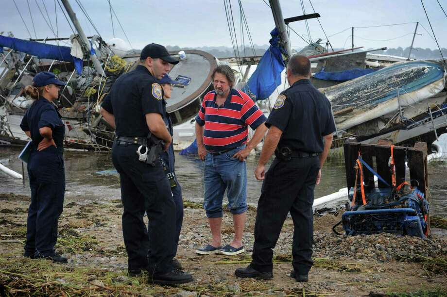 Weston resident Ed Train talks to Westport police and the United States Coast Guard about his sailboat iwshed washed ashore again Tuesday, September 11, 2018, along Harbor Road in Westport, Conn. Train has had a contentious relationship with Saugatuck Shores residents who are annoyed that his boats often become unmoored and end up washing ashore. Photo: Erik Trautmann / Hearst Connecticut Media / Norwalk Hour