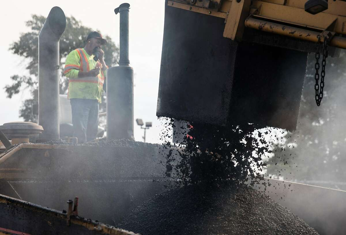 Workers pour asphalt for the rapid-bus system, one of the thousands of projects receiving funds from the gas-tax increase.