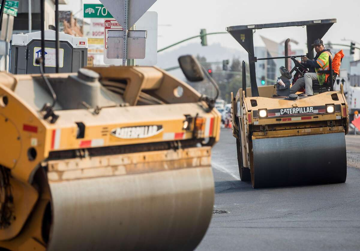 Construction crews smooth the asphalt for a rapid-bus system along a strip of International Boulevard from Uptown Oakland to the San Leandro border.
