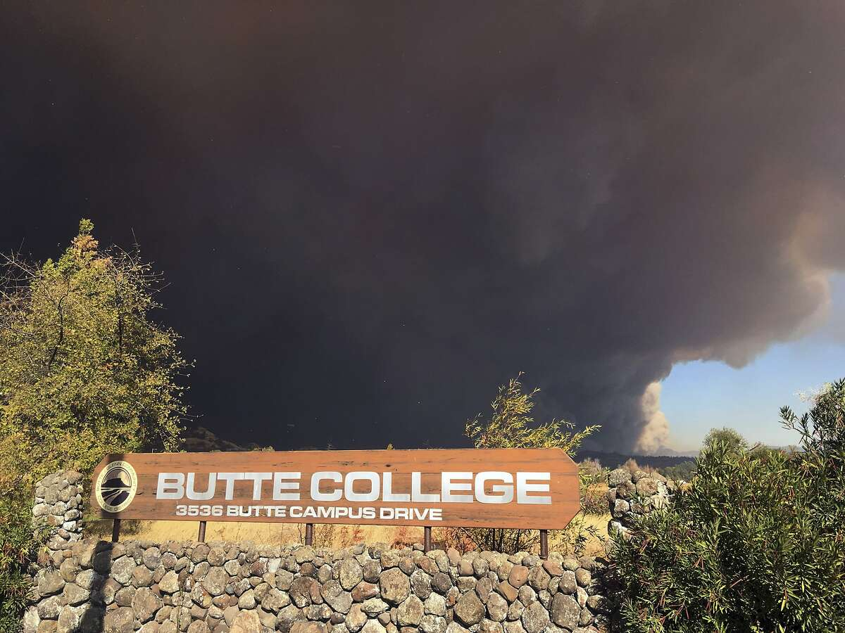 Smoke from the Camp Fire, burning in the Feather River Canyon near Paradise, Calif., darkens the sky above the Butte College sign in Oroville, Calif., Thursday, Nov. 8, 2018. (AP Photo/Don Thompson)